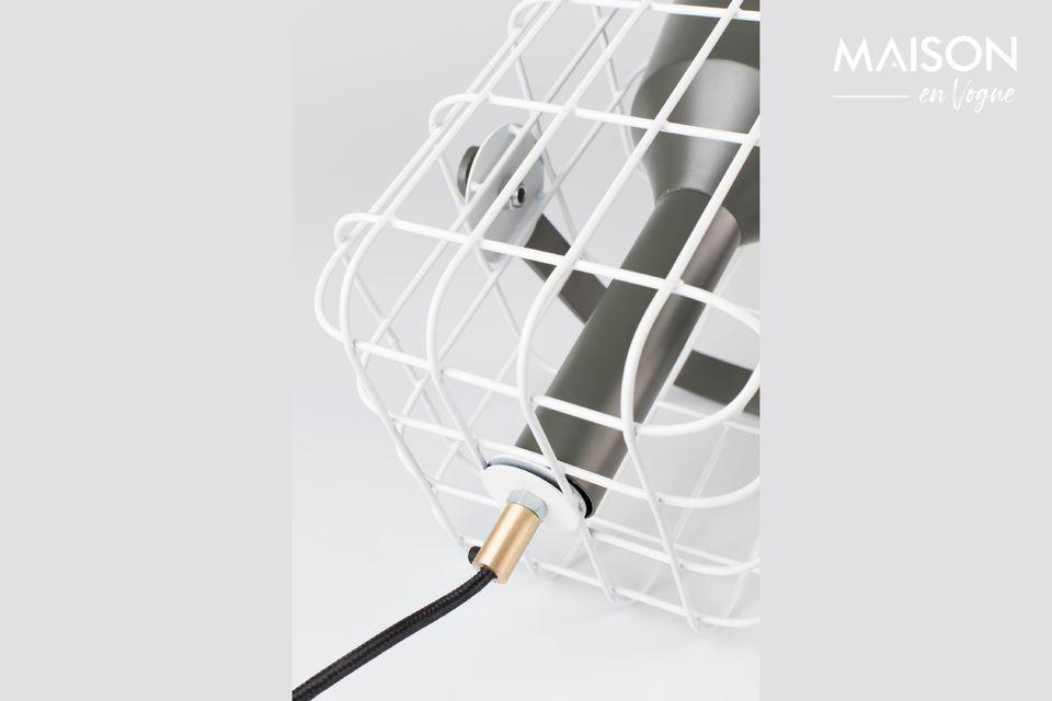 De lamp is omgeven door een witte kooi in gelakt ijzer die aangenaam is om naar te kijken